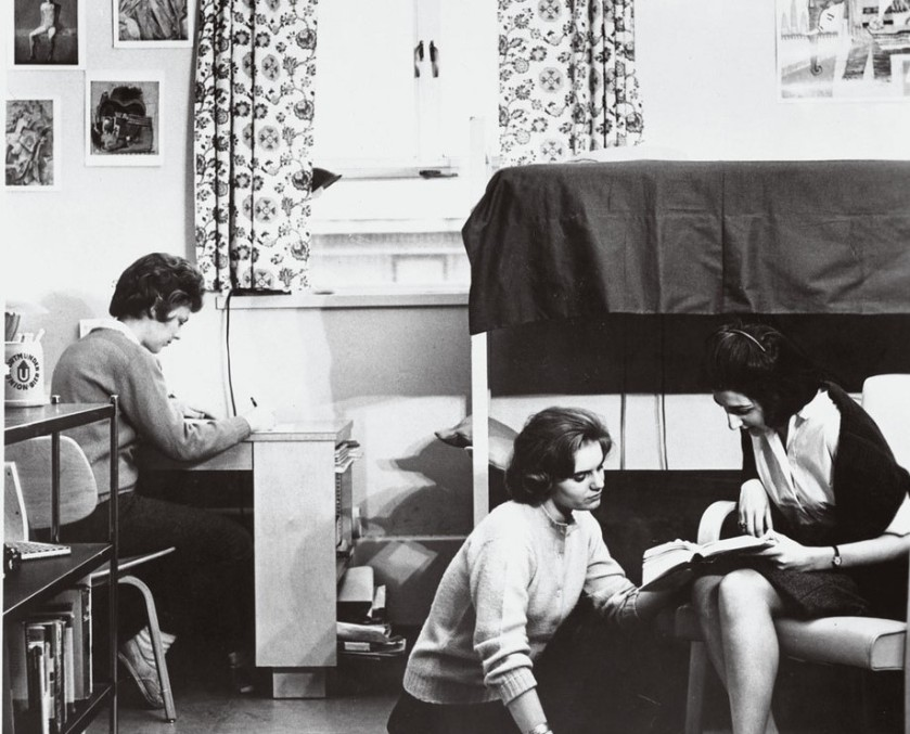 Black and white image of three women. One is sitting at a desk on the left, writing. The other two are sitting on the right, in front of a canopy bed, looking at a book. One is sitting on the ground and the other is sitting on a chair.